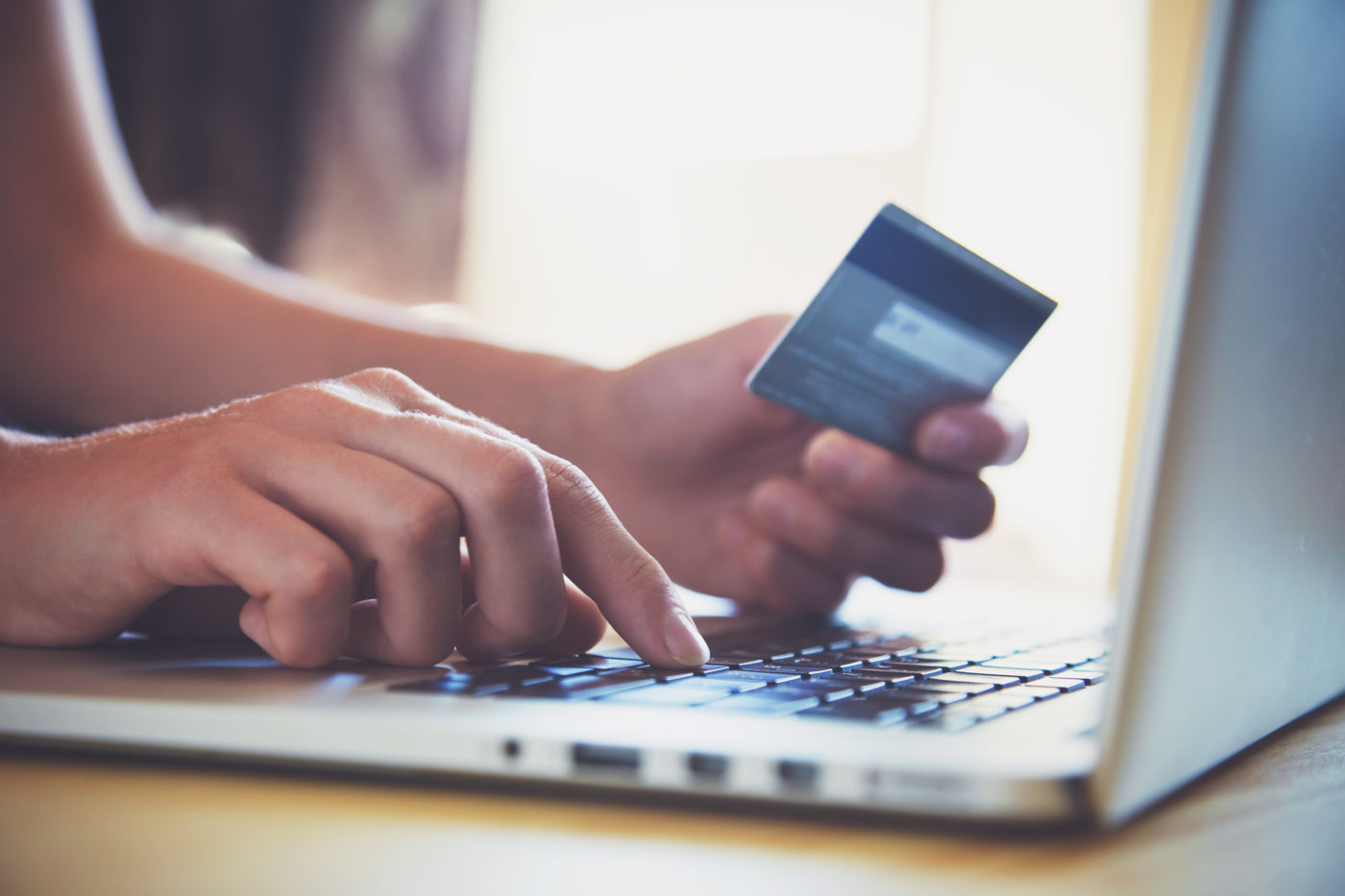 person using credit cards on laptop